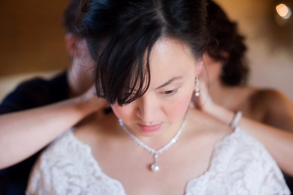 Bride putting necklace on