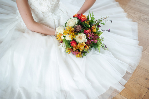 Bride sitting holding colourful wedding bouquet