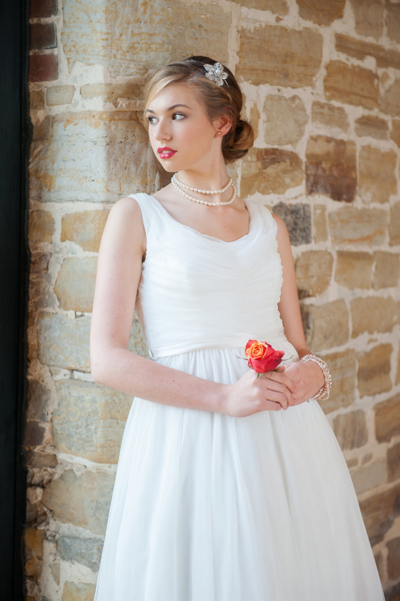 Bride holding flower and leaning against wall