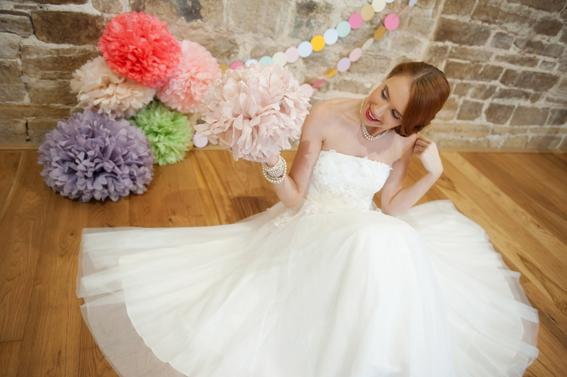 Bride sitting holding paper pom pom