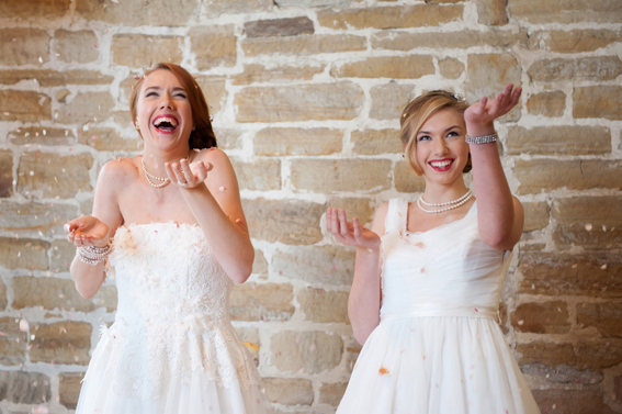 Two brides throwing confetti