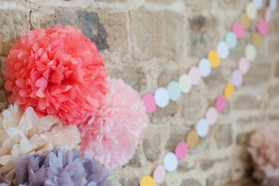 Coloured paper pom poms hanging from wall