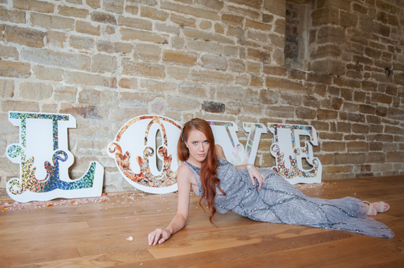 Bride laying in front of LOVE letters