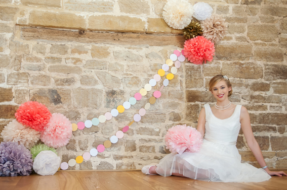 Bride sitting next to colourful paper pom poms and garland