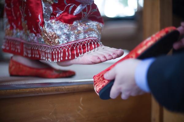 Groom putting shoe on bride's foot
