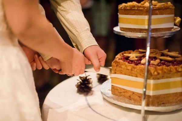 Bride and groom cutting pork pie wedding cake