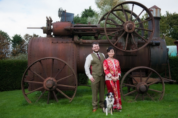 Bride and groom in front of old farm steam engine
