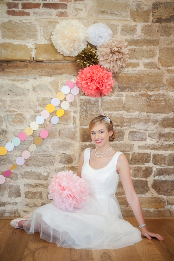 Bride sitting in front of colourful paper pom poms and garland
