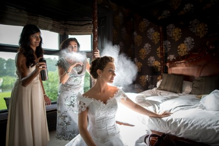 Bridesmaid spaying bride's hair with hairspray - Picture by Karli Harrison Photography