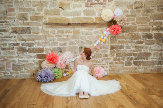 Bride sitting next to coloured paper pom poms