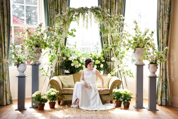 Bride sitting on sofa surrounded by spring flowers