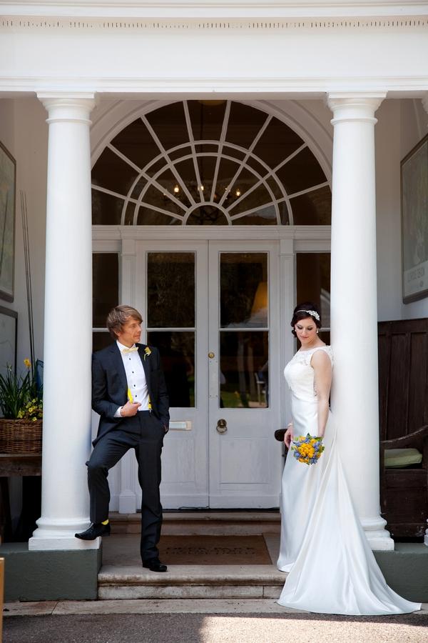Bride and groom leaning on pillars of Deer Park Hotel