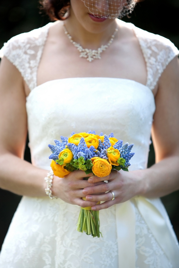 Bride holding yellow and blue bouquet