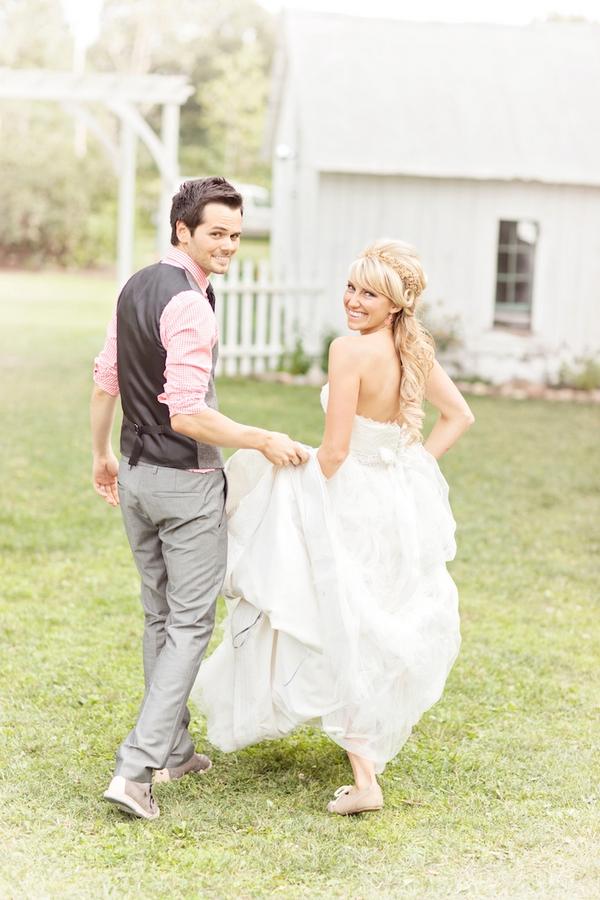 Groom holding up bride's dress