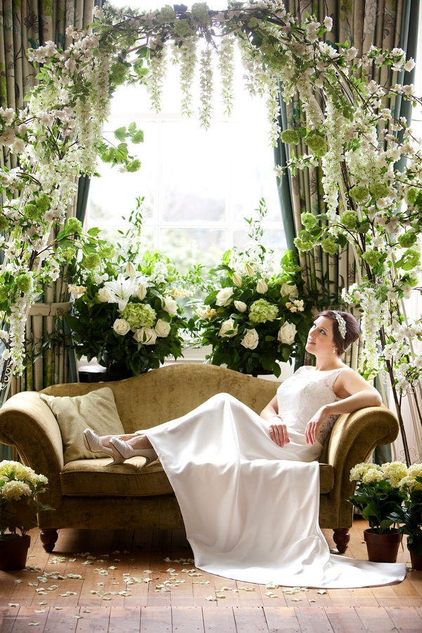 Bride laying on sofa surrounded by spring flowers