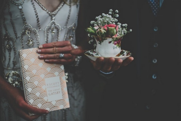 Bride and groom holding book and teacup