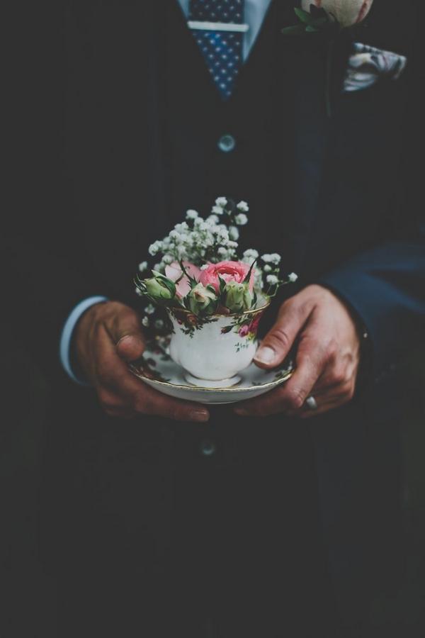 Groom holding vintage teacup