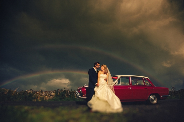 Bride and groom standing by car with dark clouds and rainbow in background - Picture by DSB Creative