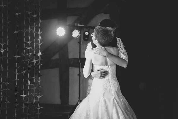 Bride and groom hug on dance floor