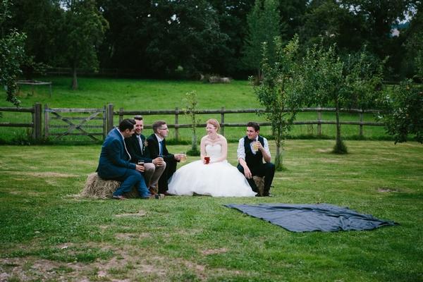 Bride and groomsmen sitting on hay bale