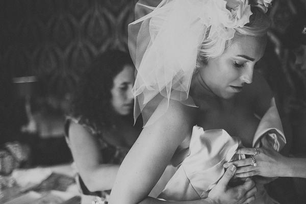 Bride putting Vivienne Westwood wedding dress on