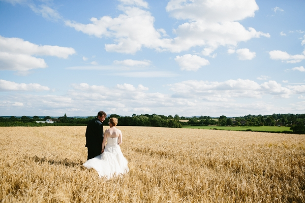 Bride and groom walking across corn field