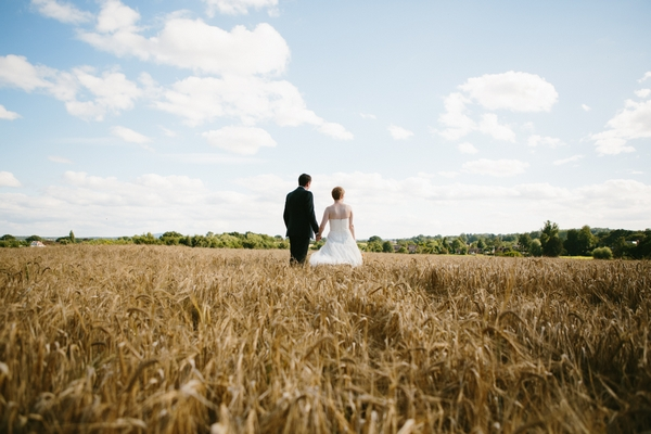 Bride and groom walking in corn field