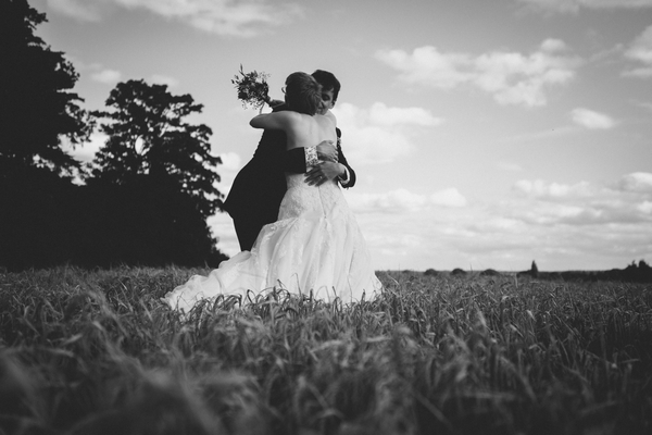 Bride and groom hugging in corn field