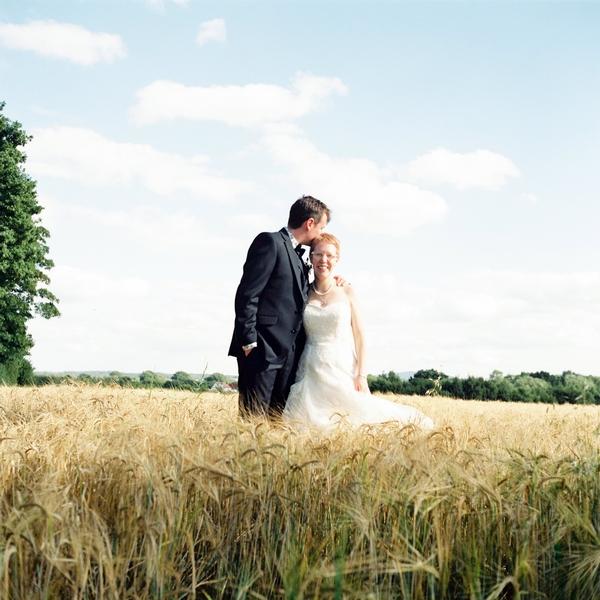 Groom kissing bride's head in corn field