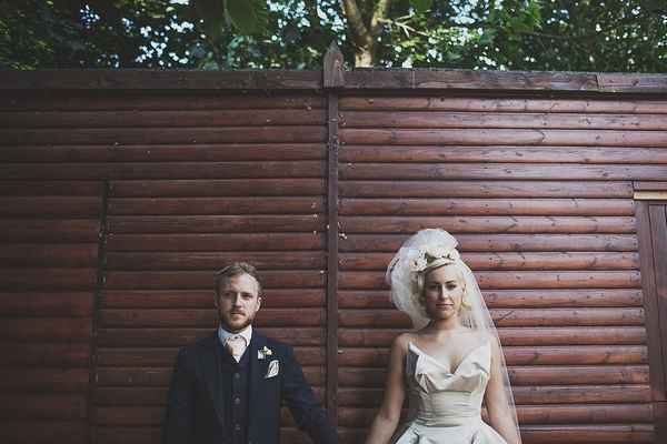 Bride and groom in front of fence