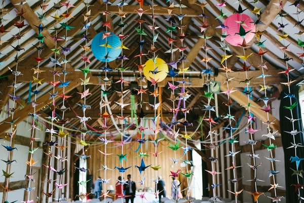 Colourful decorations hanging from ciling at wedding