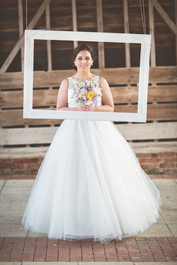 Bride standing behind picture frame