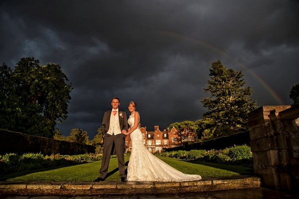 Bride and groom with dark sky and rainbow - Picture by Andy Fountain Photography