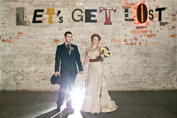 Steampunk bride and groom in front of wall with Lets Get Lost written on