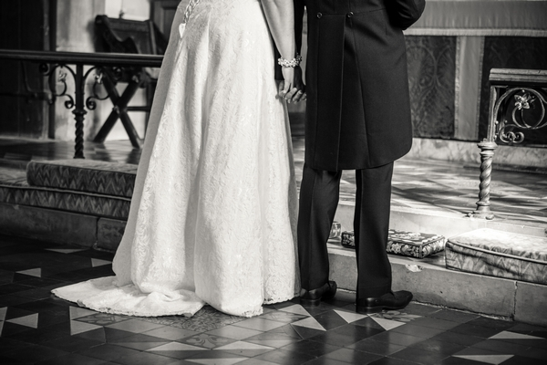 Bride and groom holding hands at altar