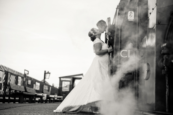 Bride and groom kissing on train