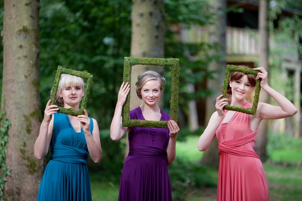 Bridesmaids holding picture frames in front of faces