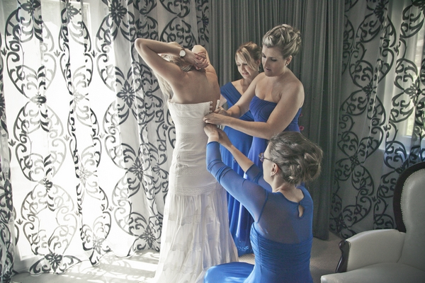 Bridesmaids doing up bride's wedding dress
