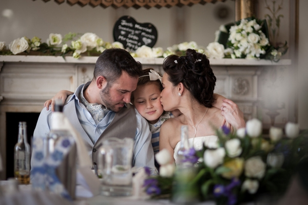 Young girl hugging bride nd groom - Picture by Linus Moran Photography