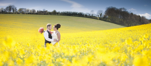 Bride and groom in field of yellow flowers - Picture by Linus Moran Photography