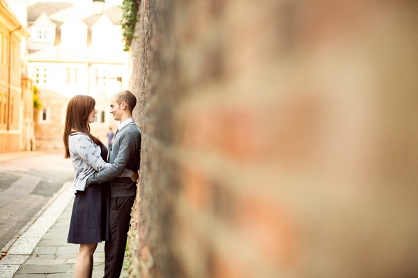Man and woman leaning up against wall
