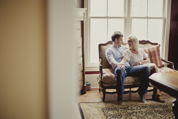 Engaged couple sitting on couch