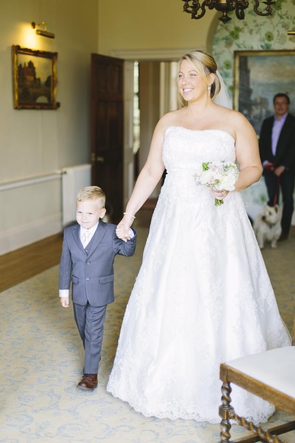Bride walking into wedding ceremony with son