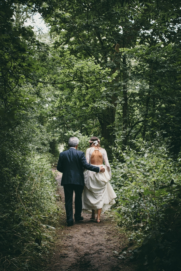 Bride being led to wedding ceremony in woods