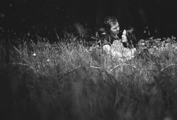 Engaged couple laying in grass