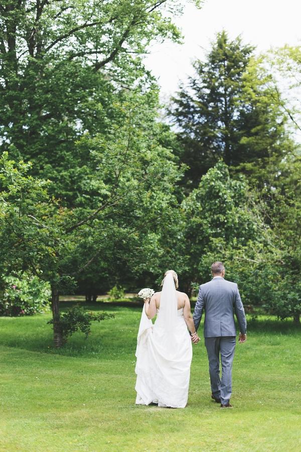 Bride and groom walking in gardens of Deer Park Country House Hotel