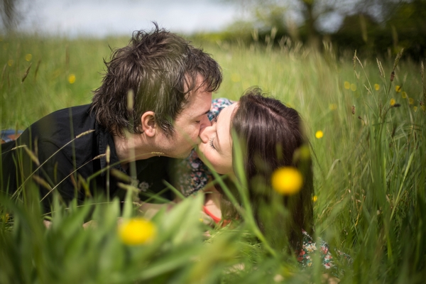 Engaged couple laying on ground kissing