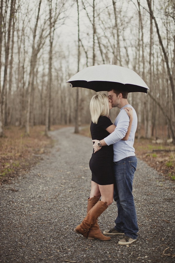 Engaged couple kissing under umbrella