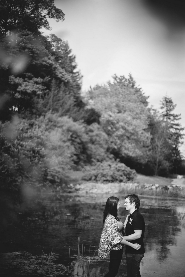 Engaged couple standing by lake