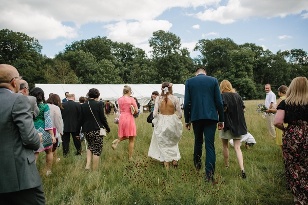 Wedding party walking to marquee